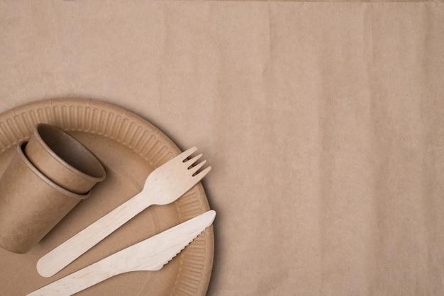 In alto sopra la foto vista dall'alto di posate in legno e bicchieri di carta e piatto collocati nell'angolo in basso a sinistra isolato su un tavolo di sfondo di carta artigianale