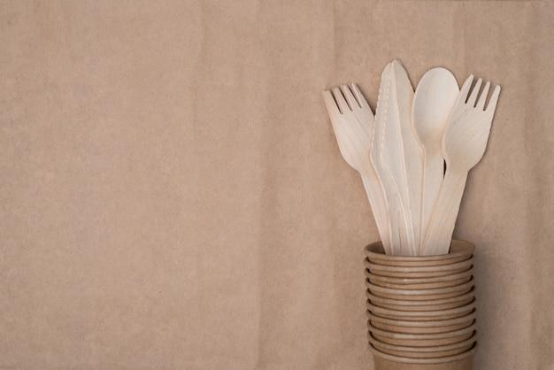 Vista dall'alto in alto foto di posate in legno poste all'interno di una pila di bicchieri di carta sul lato destro isolato su un tavolo di sfondo di carta artigianale