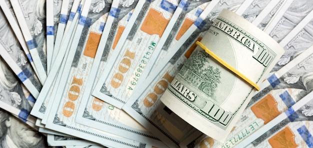 Vista dall'alto di 100 banconote in dollari arrotolate su sfondo realizzato con banconote da cento dollari. concetto di business