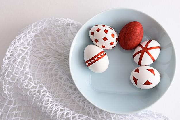 Uova di pasqua astratte di vista dall'alto con motivi geometrici rossi nel piatto blu sulla borsa ecologica della maglia bianca