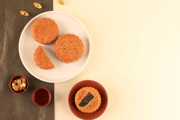 Vista dall'alto abstract still life mid autumn festival snack torta di luna su sfondo crema con giovane albero di bambù, messa a fuoco selezionata, spazio di copia