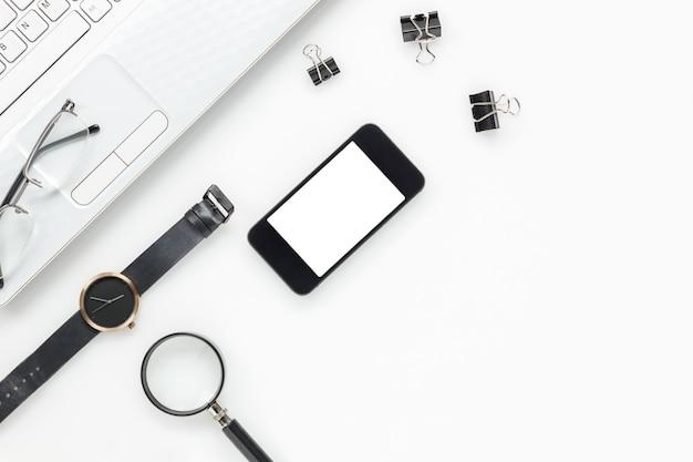 Vista superiore degli accessori business office desk.mobile telefono, computer portatile, orologio, appunti, occhiali da vista, lente d'ingrandimento su bianco scrivania con copia spazio.