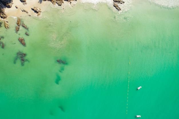 Foto aerea vista dall'alto dal drone volante di un paesaggio di superficie del mare incredibilmente bello con spazio copia acqua turchese per il tuo messaggio di testo pubblicitario sfondo di viaggio mare estivo.