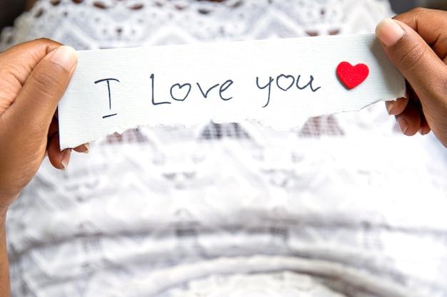 Vista dall'alto di una donna afro in abito bianco con in mano un messaggio cartaceo ti amo. concetto di san valentino.