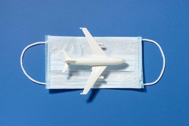 Vista dall'alto della statuetta dell'aeroplano con mascherina medica