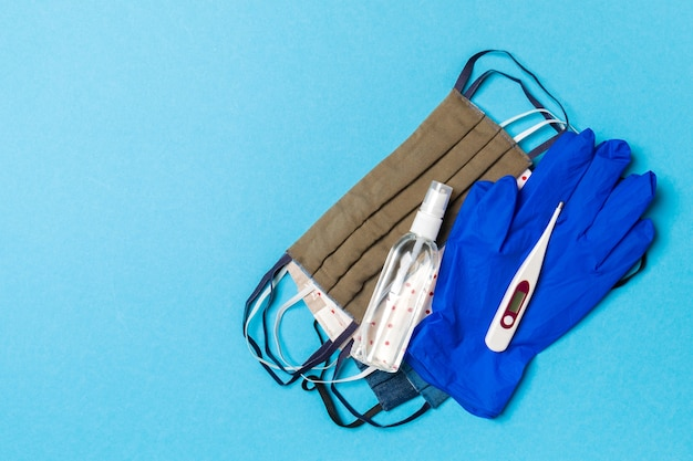 Vista dall'alto di disinfettante per le mani con alcol, guanti in lattice, termometro digitale e maschere riutilizzabili fatte a mano sulla superficie blu