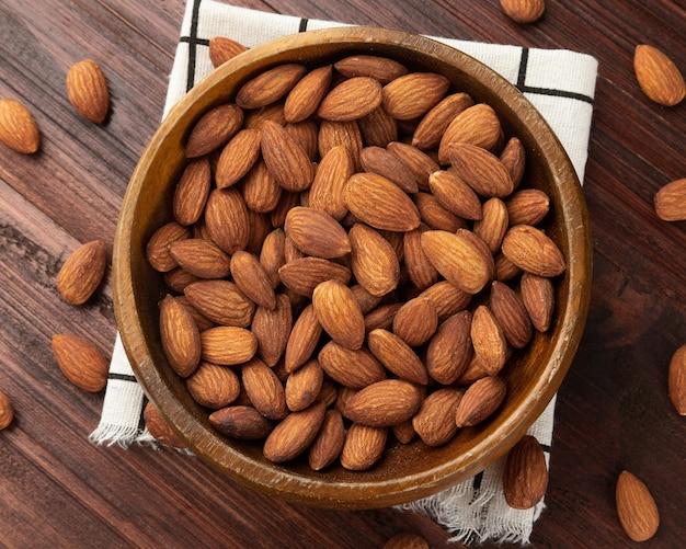Vista dall'alto delle mandorle in una ciotola di legno sul tavolo, piatto, spuntino sano, cibo vegetariano.