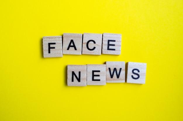 Vista dall'alto di blocchi di alfabeto con lettere su sfondo giallo brillante. faccia di notizie - scritte.
