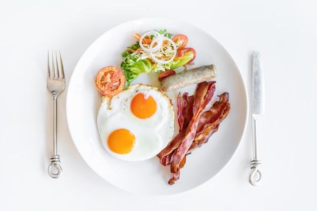 Vista dall'alto della colazione americana con forchetta e coltello su bianco