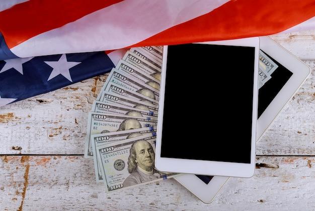 Bandiera americana di vista superiore sui dollari americani usa economica su una compressa digitale