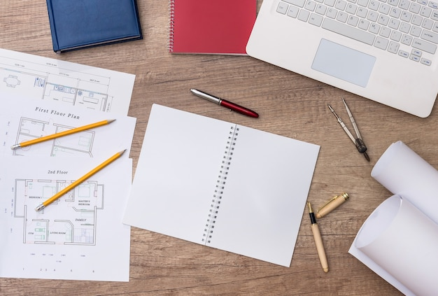 Vista dall'alto del posto di lavoro dell'architetto con progetto, laptop e rotoli