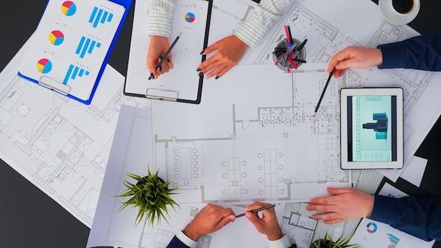 Vista dall'alto di architetti e ingegneri che creano un progetto per costruire un edificio moderno dotato delle competenze per correggere errori e dare suggerimenti durante la costruzione