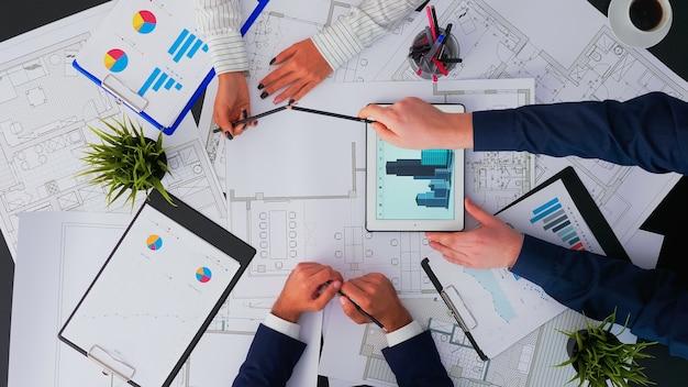 Vista dall'alto di architetti e interior designer che si incontrano per ispezionare e concludere con il progetto di ristrutturazione del cambiamento