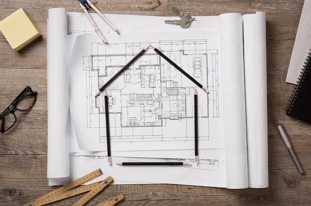 Vista dall'alto di progetti architettonici, rotoli e strumenti da disegno sul piano di lavoro.