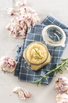 Vista dall'alto pasta di aglio aromatico in un barattolo di vetro posato su un panno da cucina rustico con bulbi e chiodi di garofano sbucciati e rosmarino.