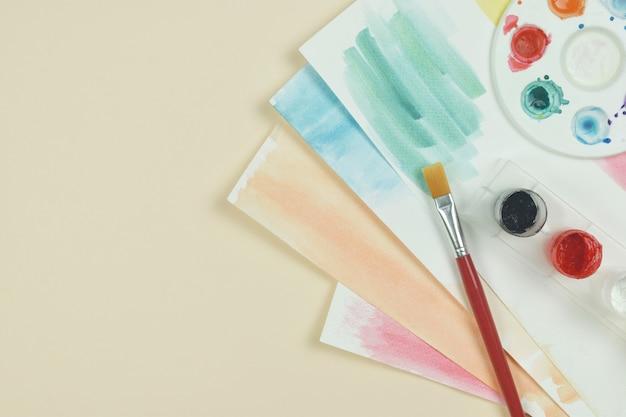 Vista dall'alto dell'acquerello della tavolozza artistica e un pennello su sfondo arancione