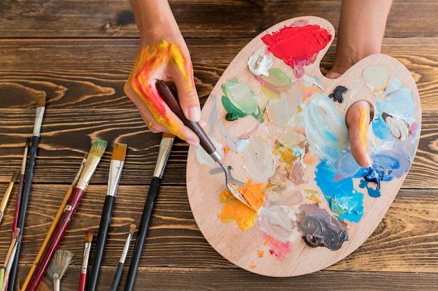 Vista dall'alto della tavolozza di vernice della holding dell'artista