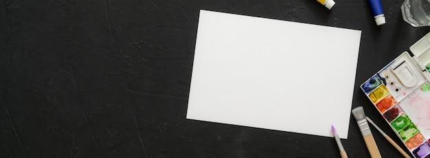 Vista dall'alto dell'area di lavoro dell'artista con carta da schizzo, strumenti di pittura e copia spazio