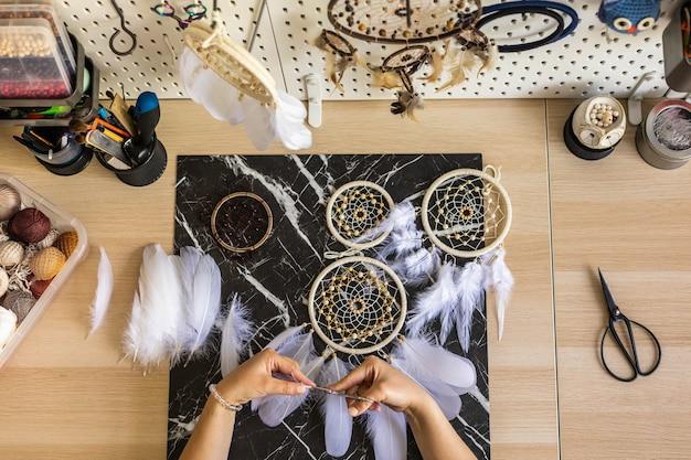 Vista dall'alto mani femminili artistiche che creano acchiappasogni con piume e filo in un cerchio pov shot