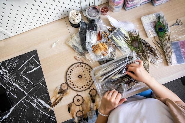 Le mani artistiche della donna vista dall'alto creano l'amuleto nativo tribale acchiappasogni usano piume naturali