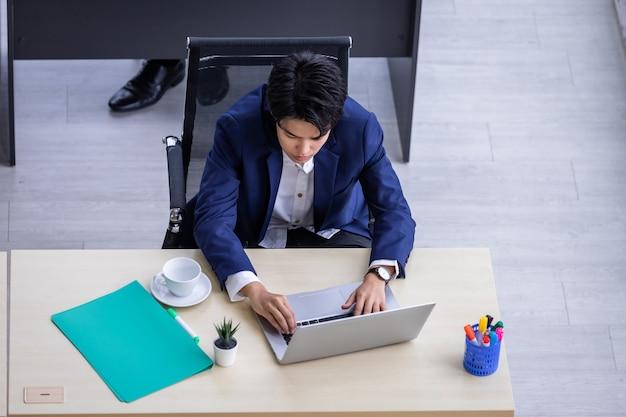 Vista dall'alto di una lesbica maschiaccio asiatica che lavora al computer portatile nella sala riunioni dell'ufficio moderno