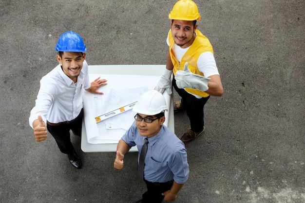 Vista dall'alto del team di ingegneri asiatici sorridente che mostra il gesto alla fotocamera con spazio per la copia