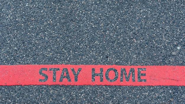 Vista dall'alto della strada asfaltata con linea rossa e testo soggiorno a casa