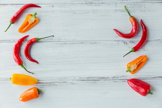 Vista dall'alto di peperoni colorati assortiti sulla tavola di legno bianca