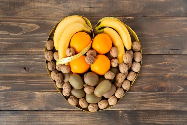 Vista dall'alto di frutta assortita e frutta secca che formano un cuore su un tavolo di legno scuro. mangiare sano e concetto di benessere.