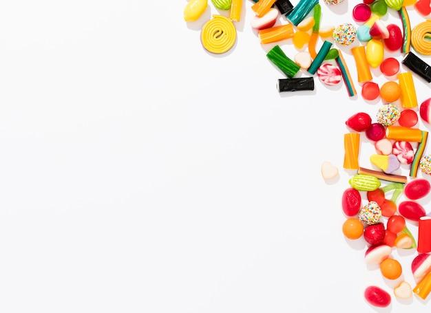 Assortimento di vista dall'alto di caramelle colorate su sfondo bianco con spazio di copia