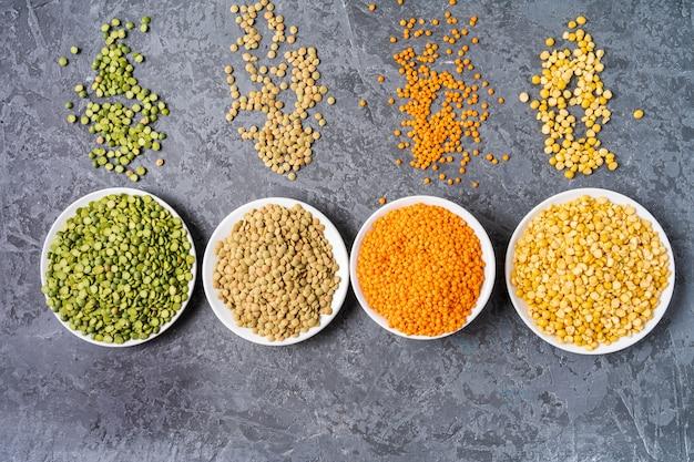 Vista dall'alto di assortimento di piselli, lenticchie e legumi su sfondo grigio.