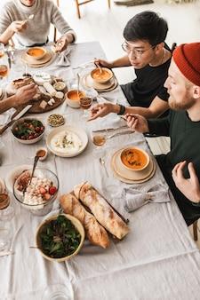 Vista dall'alto di un attraente gruppo di amici internazionali seduti al tavolo pieno di cibo che mangia insieme