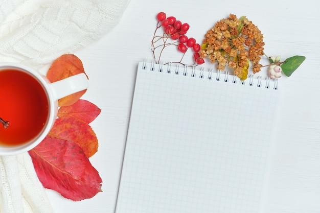 Vista dall'alto concetto di autunno con sfondo in legno e blocco note