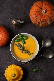 Vista dall'alto della zuppa di spezie di zucca autunnale con semi di zucca e olio d'oliva su sfondo scuro strutturato