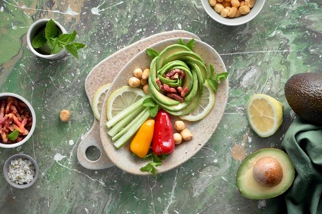 Vista superiore dell'insalata di rose di avocado con cubetti di pancetta e formaggio affumicato su sfondo verde astratto