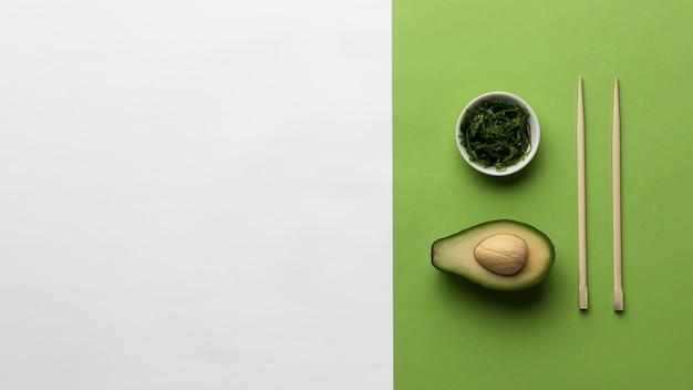 Vista dall'alto di avocado con ciotola di verdure e copia spazio