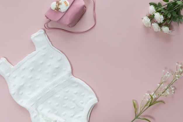 Vista superiore del fondo degli accessori della neonata, della tuta del corpo del bambino, della borsa, dei fiori e dei giocattoli sopra fondo rosa con lo spazio della copia; vista dall'alto, piatta