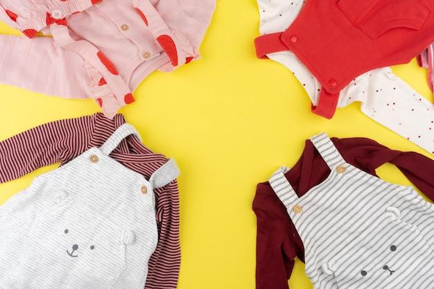 Vista dall'alto di vestiti della neonata su sfondo giallo