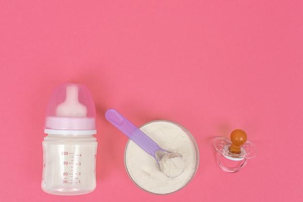 Vista dall'alto di latte in polvere per bambini, biberon e manichino su uno sfondo rosa
