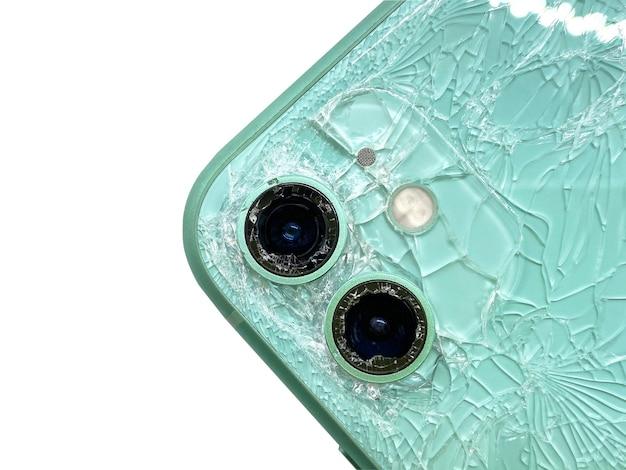 Vista dall'alto sul retro dello smartphone moderno verde con un vetro rotto e un primo piano della fotocamera danneggiato isolato