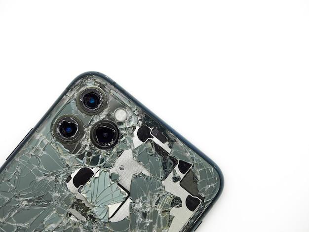 Vista dall'alto sul retro dello smartphone moderno verde mezzanotte con un vetro rotto e un primo piano della fotocamera danneggiato isolato su priorità bassa bianca