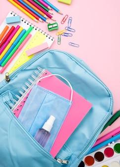 Vista dall'alto di ritorno a scuola elementi essenziali con matite e quaderno