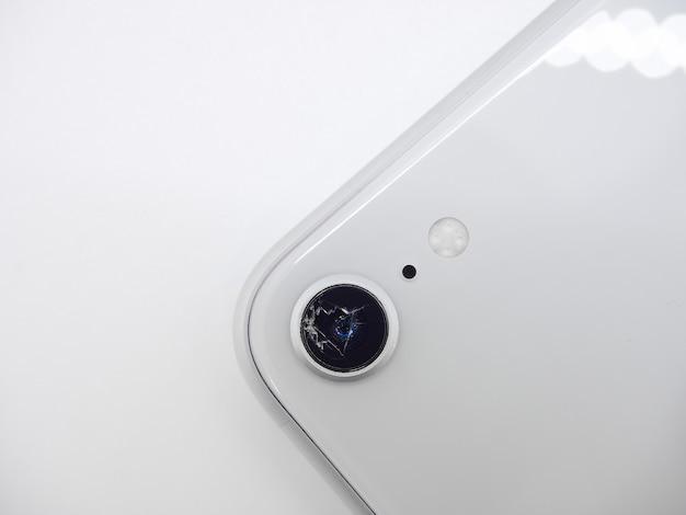 Vista dall'alto sul retro dello smartphone moderno bianco con un primo piano di vetro rotto della fotocamera isolato su superficie bianca