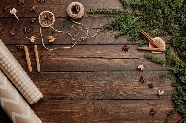 Vista dall'alto sfondo di forniture per confezioni regalo di natale su tavola in legno rustico decorato con abete tr...