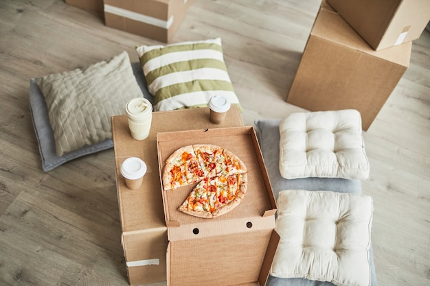 Immagine di sfondo vista dall'alto della pizza su scatola di cartone come tavolo improvvisato nella stanza vuota mentre la fami...