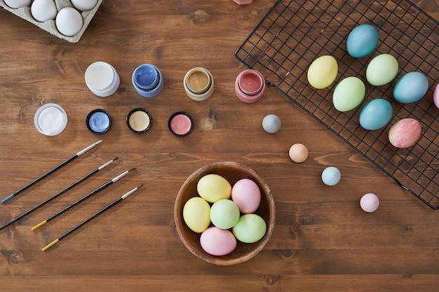 Vista dall'alto sfondo di uova di pasqua color pastello su tavola di legno e forniture artistiche, decorazioni pasquali fai da te, spazio copia