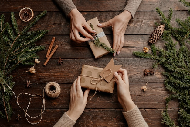 Sfondo vista dall'alto con due giovani donne irriconoscibili che incartano i regali di natale al tavolo di legno ...