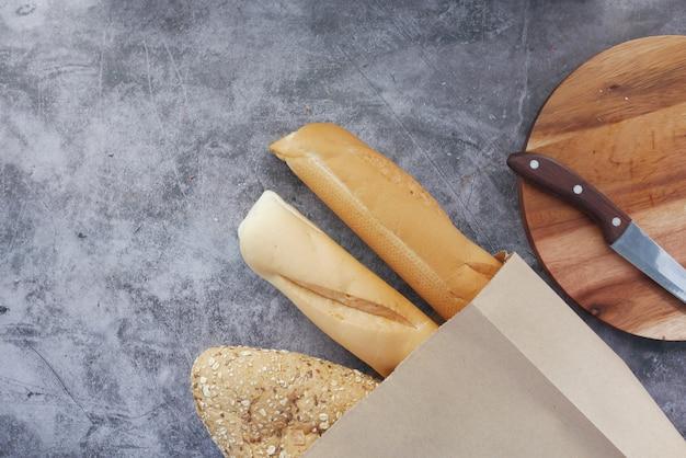 Vista dall'alto del pane cotto in un sacchetto di carta su sfondo nero