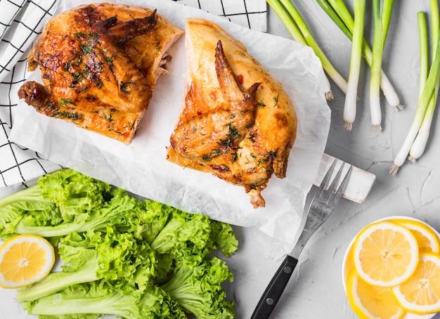 Vista dall'alto di pollo intero al forno a metà con insalata