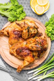 Vista dall'alto pollo intero al forno con fette di limone, cipolla verde e insalata